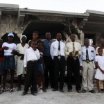 Terremoto en Haiti. Familia rezando delante de su casa destruida